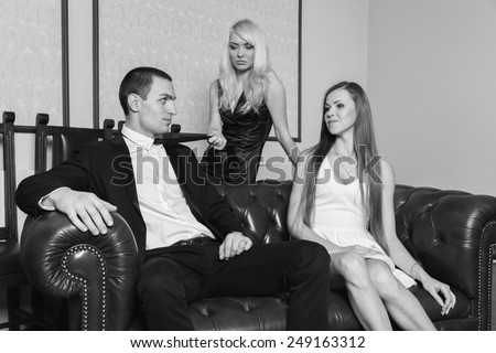 A guy and two girls in the room, tense. Group young people  enjoy the evening. Human feelings - jealousy, love, passion, betrayal. - stock photo