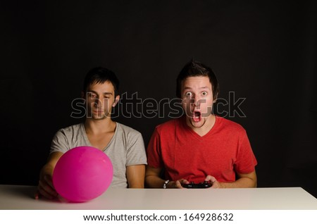 A guy bored to his bones next to his gaming buddy - stock photo