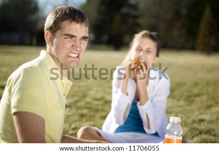 A guy cringing as his date stuff her face with food. - stock photo