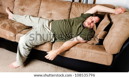 A guy flung all over the couch - stock photo
