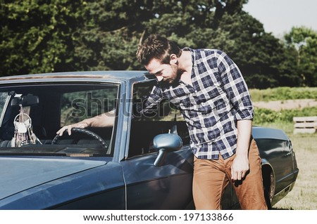 A guy in a plaid shirt touches his steering wheel.