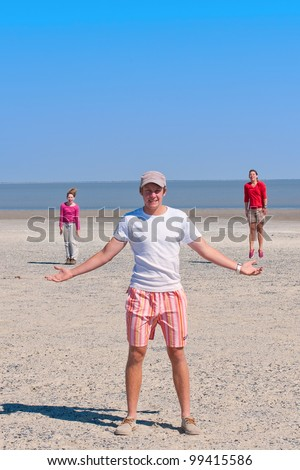 a guy standing with girls jumping - stock photo