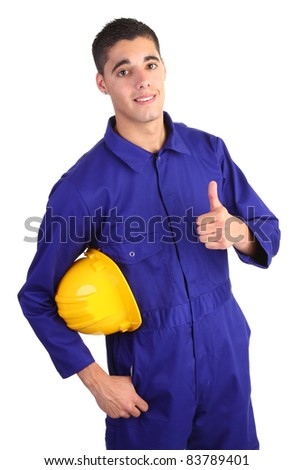 A guy wearing overals and holding a hardhat with a thumbs up sign. - stock photo