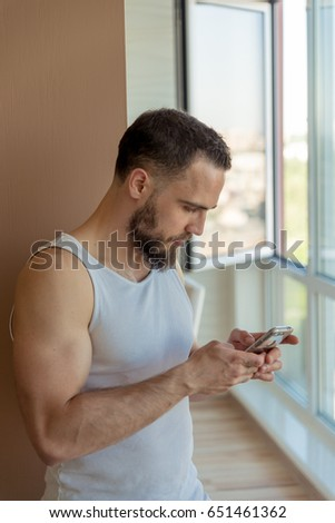 A guy with a beard looks at the phone
