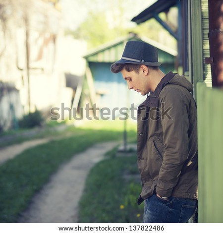 a guy with a fashionable hairstyle is waiting outdoors - stock photo