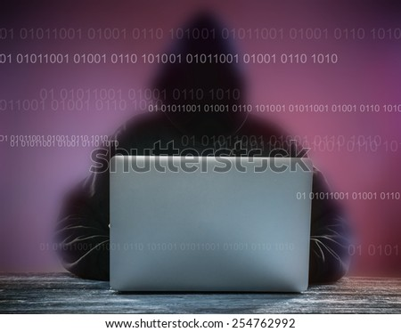 A hacker with a hood with laptop. Online network danger. - stock photo