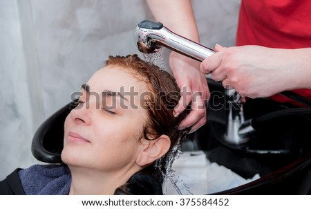A hairdresser rinsing hair of a woman after shampooing. Selective focus. - stock photo