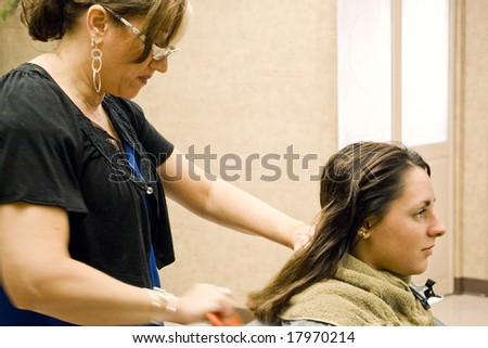 A hairdresser working on a clients hair at the salon. - stock photo