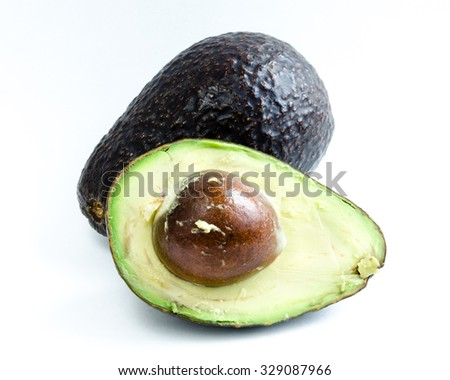 A half cut with seed and a whole organic fresh ripe avocado isolated on white background