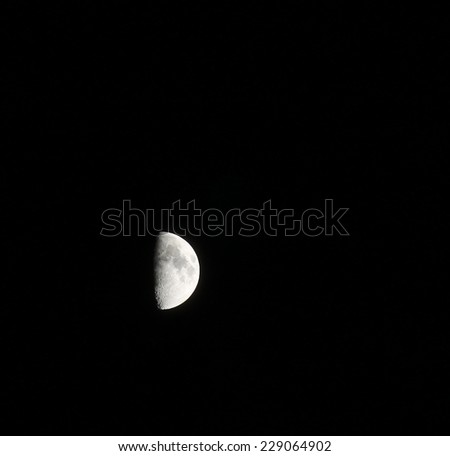 A half moon high in the night sky on a cool fall night - stock photo