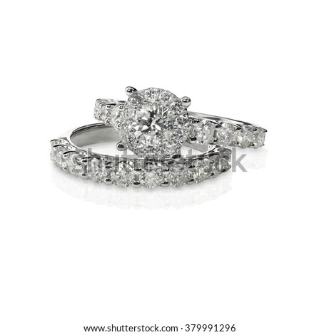 A halo setting solitaire set. Cluster stack of diamond wedding engagement rings isolated on white - stock photo