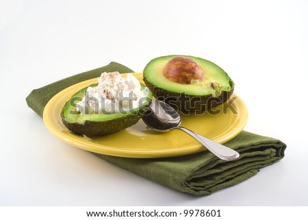 A halved avocado filled with cottage cheese sits next to a spoon on a yellow plate. - stock photo
