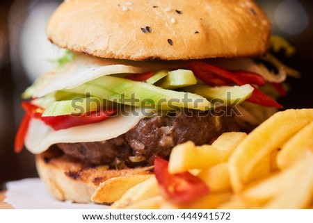 A hamburger consisting of meat patties, vegetables, cheese and French fries closeup
