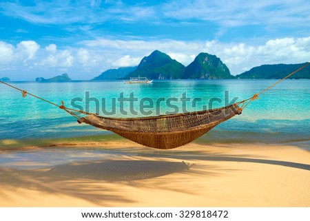 A hammock at the beach with the view of Bacuit Archipelago islands (El Nido, Philippines) - stock photo