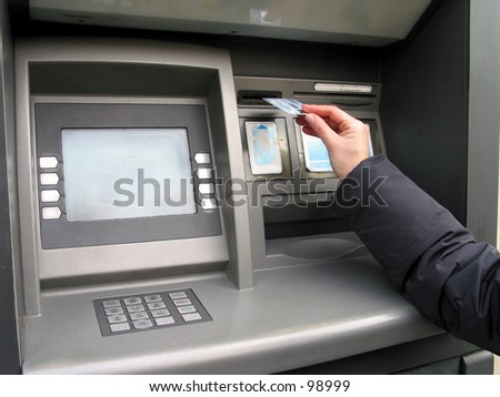 a hand, a credit card and ATM, trying to get money.