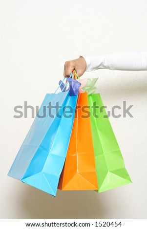 A hand carrying shopping bags - stock photo