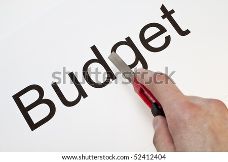 A hand cutting the word budget with a stanley knife - stock photo