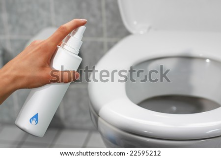 a hand disinfecting a toilet using a spray - stock photo