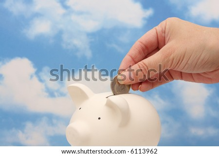A hand dropping coins into piggy bank