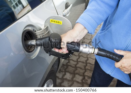 A hand filling up a car with diesel - stock photo