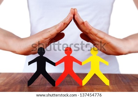a hand forms a roof and symbolizes the protection of colorful paper chain figures, isolated - stock photo