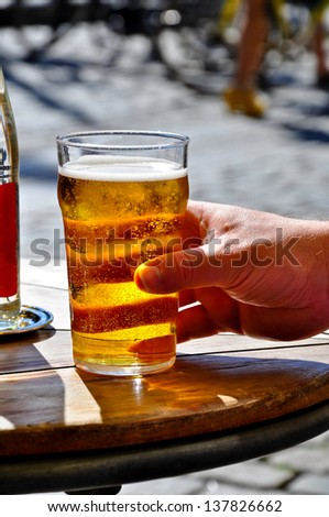 A hand grabbing a glass of beer - stock photo