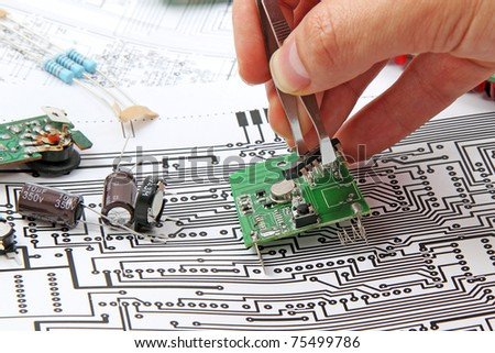 A hand hand with tweezers holding a electronic circuit board  on the background of electronic scheme - stock photo