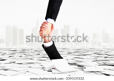 A hand helps another not to go down into bureaucracy - stock photo