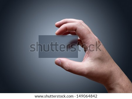 A hand holding a blank transparent business card. - stock photo