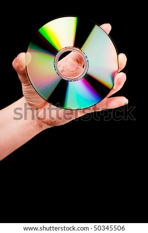 A hand holding a CD on black background - stock photo