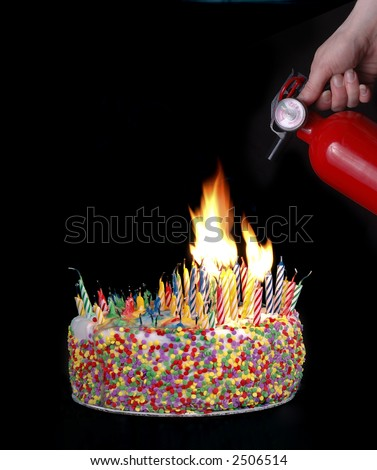 A hand holding a fire extinguisher above a cake with candles creating a fire.