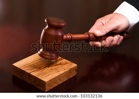 A hand holding a gavel - stock photo