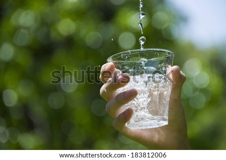 A hand holding a glass of water against a green background. - stock photo