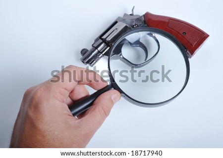 A hand holding a magnifying-glass over a gun