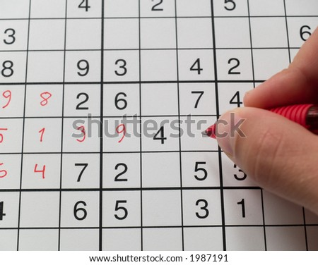 A hand holding a pen on a sudoku grid. - stock photo
