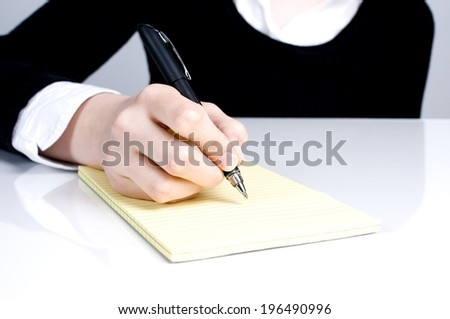 A hand holding a pen over a lined pad of paper. - stock photo