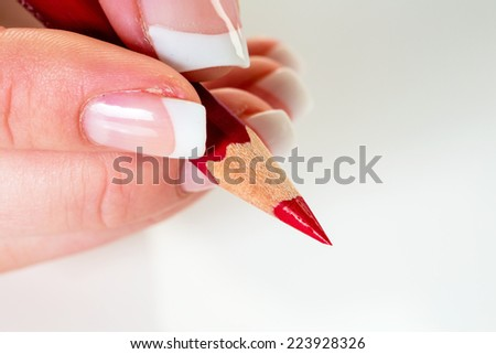 a hand holding a red pen. symbol photo for savings and budget cuts.