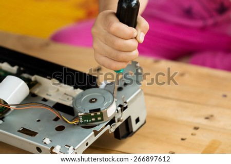 A hand holding a screwdriver is installing or repairing part of computer components - stock photo