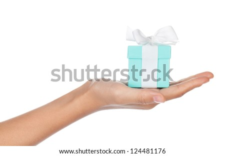 A hand holding a small blue box with a white ribbon in its palm isolated on white. - stock photo
