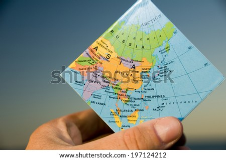 A hand holding a small square of map that shows the Asian continent. - stock photo