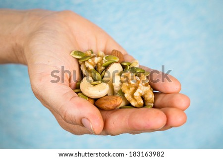 A hand holding a wide variety of nuts and seeds.