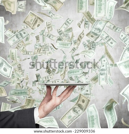 A hand holding an electronic device over the falling dollars. - stock photo
