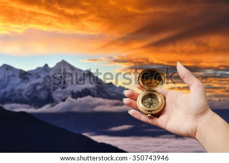A hand holding an old vintage compass. Dramatic sunrise in the Caucasian mountains at the background. Rocky summit covered with snow and wonderful light with sun rays and vivid yellow clouds. - stock photo