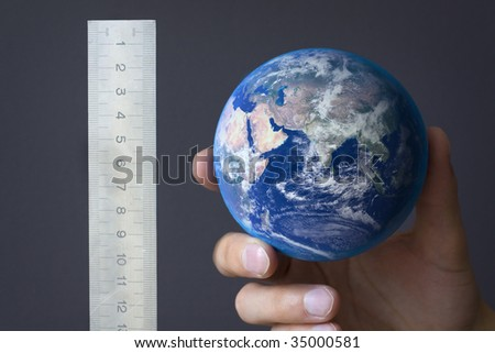 A hand holding and measuring the earth