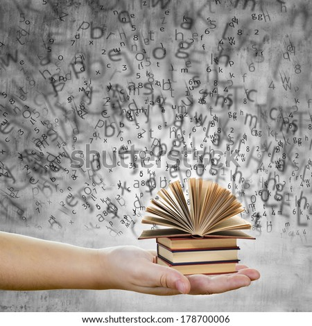 A hand holding books with words and letters representing education and knowledge concept - stock photo