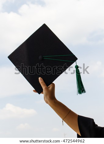 a hand holding graduation hats on background of blue sky.