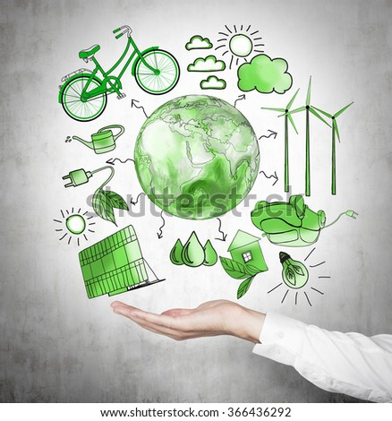 A hand holding symbols of alternative energy sources painted in green colours on a concrete wall. Green Earth in the middle. Concept of clean environment. - stock photo