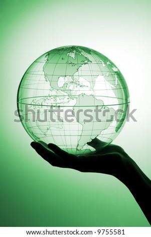 A hand holding translucent globe - stock photo