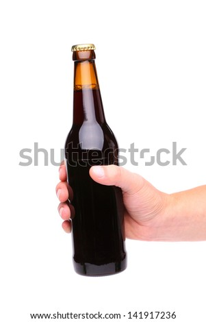 A hand holding up a brown beer bottle without label over a white background vertical format - stock photo