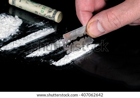 A hand holds a steel razor blade as it cuts a line of cocaine. Part of a pile of cocaine is to the left, and most of a rolled bill is at the top. Table is glass on cloth. Focus is on the razor blade. - stock photo